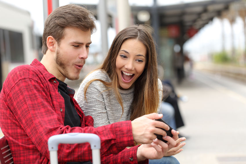 mężczyzna trzyma w dłoniach smartfon, pokazując zawartość ekranu kobiecie siedzącej obok