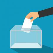 ręka wrzuca do urny swój głos wyborczy