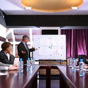 pracownicy siedzą przy stole i obradują nad wynikami firmy